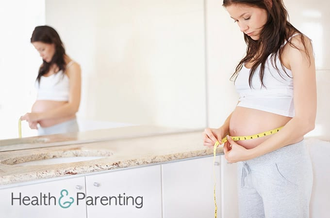 Pregnant woman measuring her belly with a tapemeasure