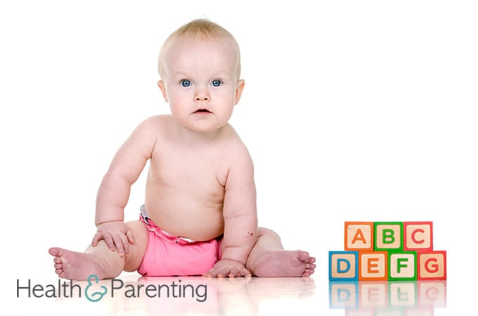 a baby sitting next to letter cubes